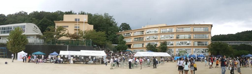 学校で行われたお祭りで大人も子供もたくさんの人たちが集まっている。販売スペースもありその前には人も集まっている。