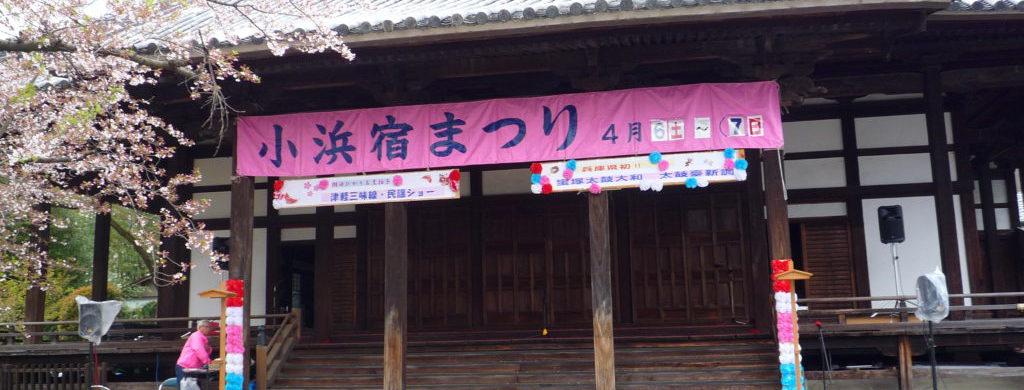 お寺の建物にピンク色の「小浜宿まつり」の横断幕が掲げられている。左手には桜の花が咲いている