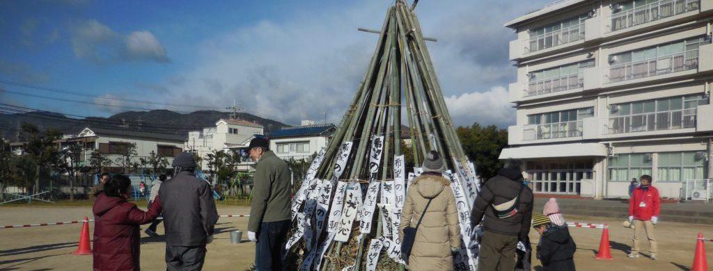 学校の校庭でとんど焼きの準備をしている。組んだ竹の前に大人や子どもが数人いて、話をしたり設置された書き初め・しめ縄飾りを見たりしている。