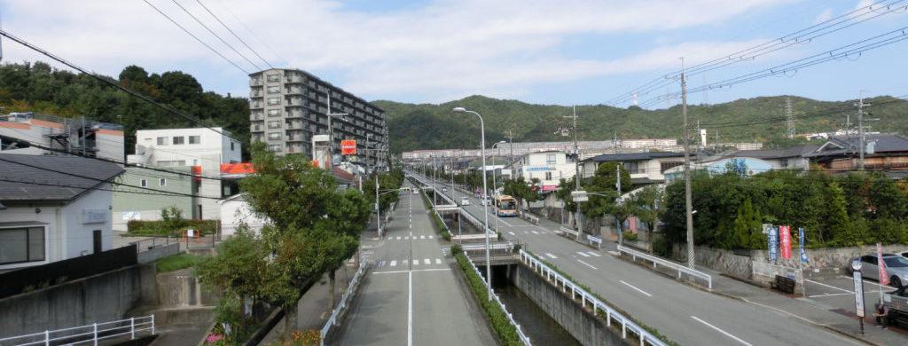 中山台の上り坂になっている道路を歩道橋の上から見ており、左右に住宅、遠方に山並みと雲混じりの青空が広がっている。