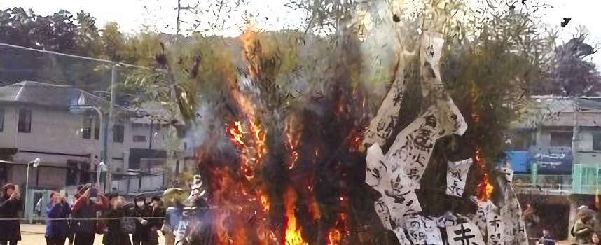 学校の運動場でとんど焼きをしていて、竹や書き初めが赤く燃えている。とんど焼きの周りで大人数人が写真を撮っている