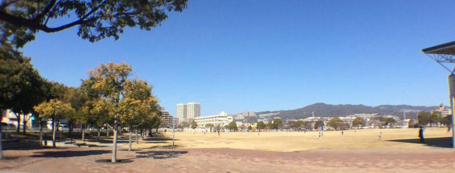 末広中央公園の広場で数人が遊んでいる姿がとても小さく見えている。青空が広がり、遠方には小学校や山並みが見える。