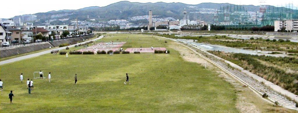 武庫川河川敷の西岸にあるテニスコートやサッカーゴールのある広場部分で何人もの人がスポーツを楽しんでいる。遠方にはゴミ処理場や山並みも見える。