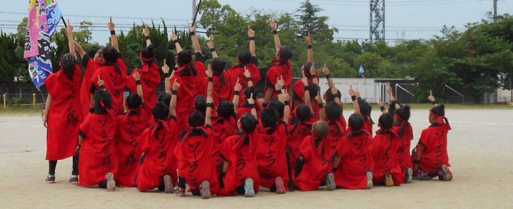学校の校庭で30人ほどの子どもたちが、背中に「ソーラン隊」と書かれたお揃いの赤い法被を着て、腕を上げ右手人差し指で空を指す同じポーズをしている