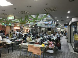カルチェヌーボ1Fの広場スペースで飲食を楽しむ多くの人々