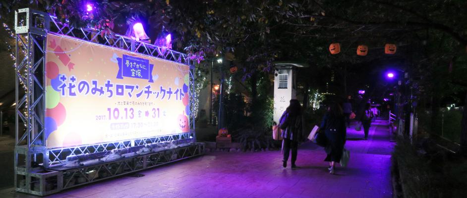花のみちに設置され、ライトアップされている「花のみちロマンチックナイト」の看板と花のみちを通る人が写っている風景