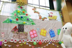 壁面にツリーやサンタ、プレゼントの飾り付けが大きくされている様子を見るまちキョン