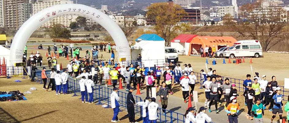 画像:第13回宝塚ハーフマラソンで河川敷を走るランナーとコース横で応援する人々の風景
