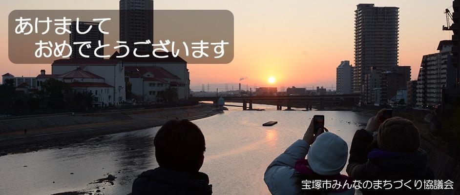 橋の上から見える初日の出を撮影する3人の人と新年の挨拶文