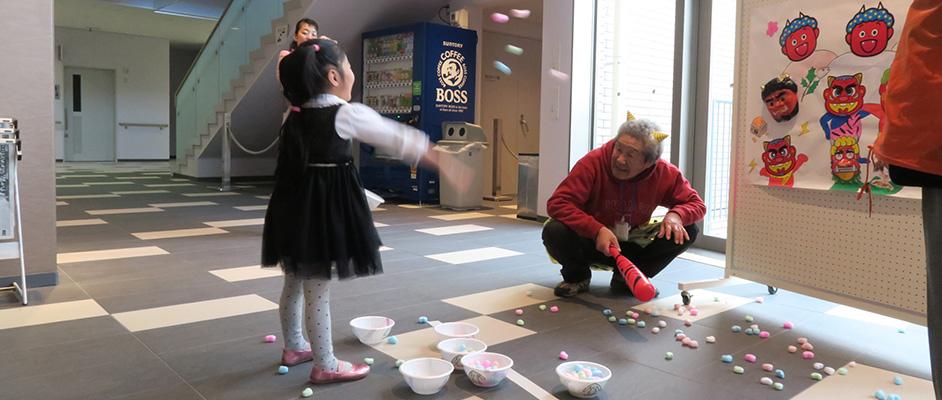 画像:節分に鬼が見守る中、鬼のお面に向かって子どもが豆の代わりの球を投げている
