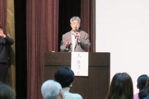 画像:演台に立って講演されている久先生