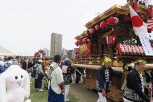 武庫川河川敷でだんじりを曳く人々と見物する周りの人達