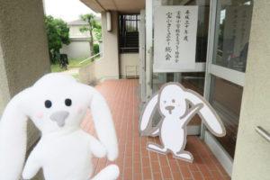宝小コミュニティの総会会場(宝塚小学校体育館)前にまちキョンの看板が立っていてまちキョンぬいぐるみが写っている