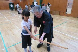 女の子が講師の男性に木刀の持ち方を教わっている