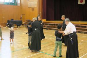 ひろい間隔で並んだ子ども達がそれぞれ講師の方に木刀の持ち方の指導を受けている