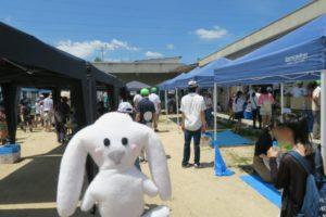 青空のもと、旧売布幼稚園のグラウンドに日よけのテントが立ち並び、各種のお店に子ども達が並んでいる