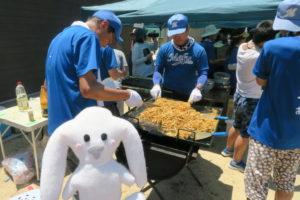 青いユニフォームの男性2、3人が大きな鉄板で山盛りの焼きそばを焼いている