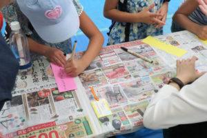 新聞をひいたテーブルの上で、短冊に標語を書いている子ども達