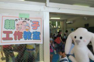入口に「作って、遊ぼう親子工作教室」の掲示があり、部屋の中に多くの親子がいる