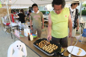 薄緑のシャツを着た男性がホットプレートでたくさんのたこ焼きを焼いて作っている