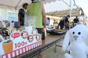 長テーブルの上にジュースやたこ焼きのイラスト入りで「4コ入りたこ焼き100円」と入った横長の小さな立て看が立てられている