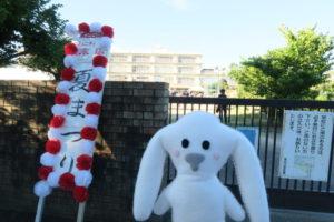 末広小学校の校門前に紅白の飾りがついた夏まつりの看板がある