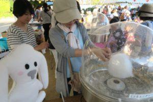 帽子を被ってタオルを巻いた女性が、専用の器具で綿菓子をくるくると大きく作っているところ