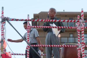 やぐらの上に2人の男性が上がって挨拶をしている。一人はコミュニティの代表