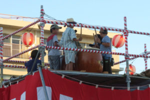 やぐらの上で4人ほどの男の子達が上向きに置かれた太鼓を一緒に叩いている