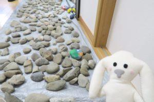 廊下に長いシートを敷き、その上にアート用の石を並べています