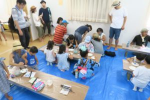 机で子ども達が石に絵を描いています