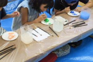 2人の女の子がそれぞれ石に水色と緑色を塗っています