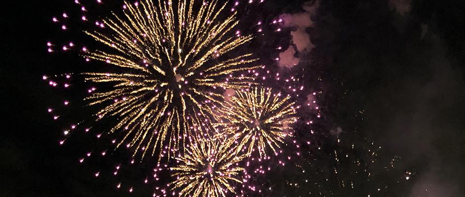 宝塚サマーフェスタ2018でオレンジ色の花火が大小3発打ち上げられ、夜空に広がっている