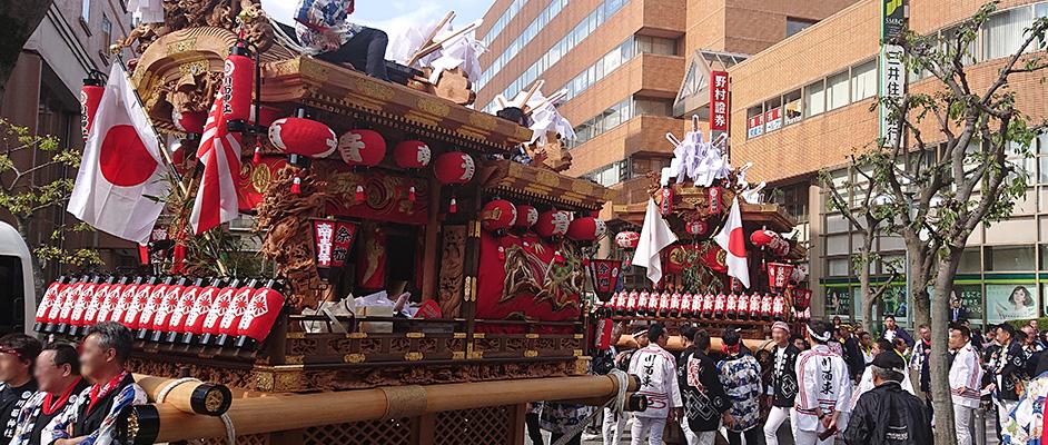 宝塚駅前の路上で曳行を待つ2台のだんじりと法被を着た引き手の方々が周りにいる風景