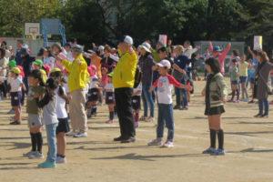 グラウンドに集まった大人や子どもたちがラジオ体操をしている