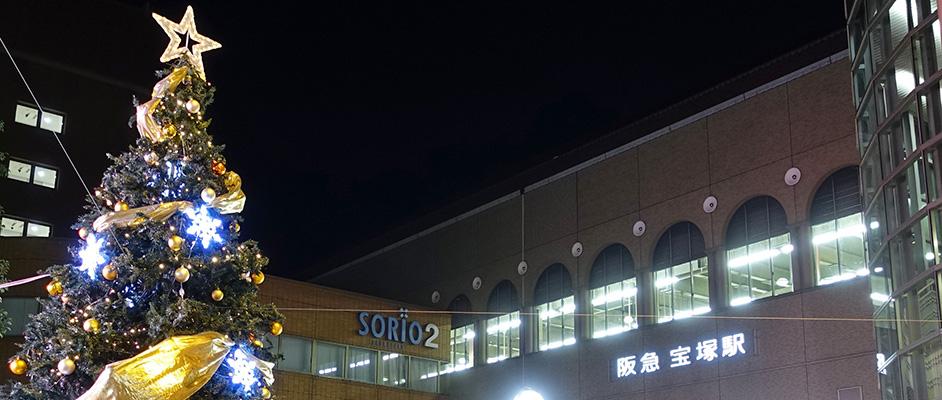 阪急宝塚駅前ゆめ広場に設置・点灯されたクリスマスツリーの上部のアップと背景に阪急宝塚駅の駅舎とロゴが光って写っている