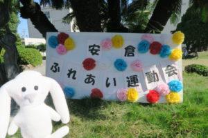 赤青黄の紙花で飾られた「安倉ふれあい運動会」の文字が入った横長の看板が木に立てかけてある
