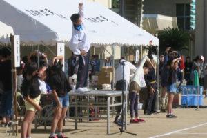 グラウンド正面の台の上で先生が、脇で4人の小学生がラジオ体操のお手本で体操をしている