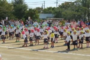 緑や赤や黄色の帽子と体操服姿の小さい子がたくさん並んで体操している