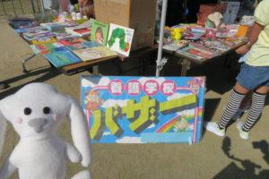 地面に置かれた養護学校のバザーの看板と、机の上に販売している絵本などが並べられている