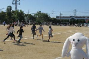 徒競走でグラウンドを走り抜ける6人の子どもたち