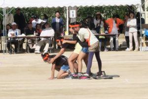 ムカデ競走で足元をつないでいるゴムチューブでうまく進めず先頭の子が地面に手を突いて止まってしまっている