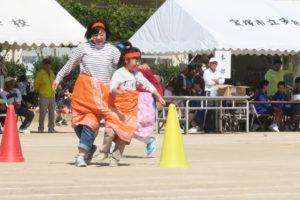 親子と見える二人組がデカパン競走でコーナーを笑顔で走り抜けている