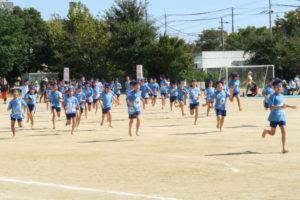水色の揃いのシャツの子どもたちが演技の最初にグラウンドに走りこんできている