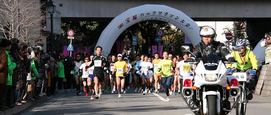 第7回宝塚ハーフマラソンのスタート付近、先導のバイクに続いてランナーが走り出しており、沿道には応援の人々が並んでいる