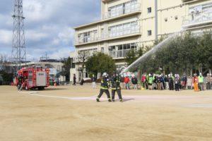 校庭に消防車が来ました。2人の消防士さんが実際にホースから放水しています