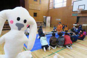 子ども達が体育館の中で消防士さんの説明を聞いています。竹で担架を作る様子を見ています