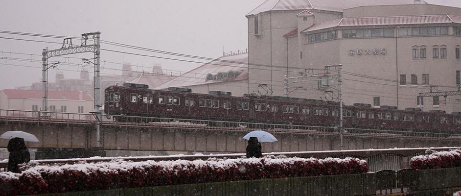 雪が降る中、阪急の列車が宝塚駅と宝塚南口駅間を走っていく様子を宝塚大橋から見ている風景
