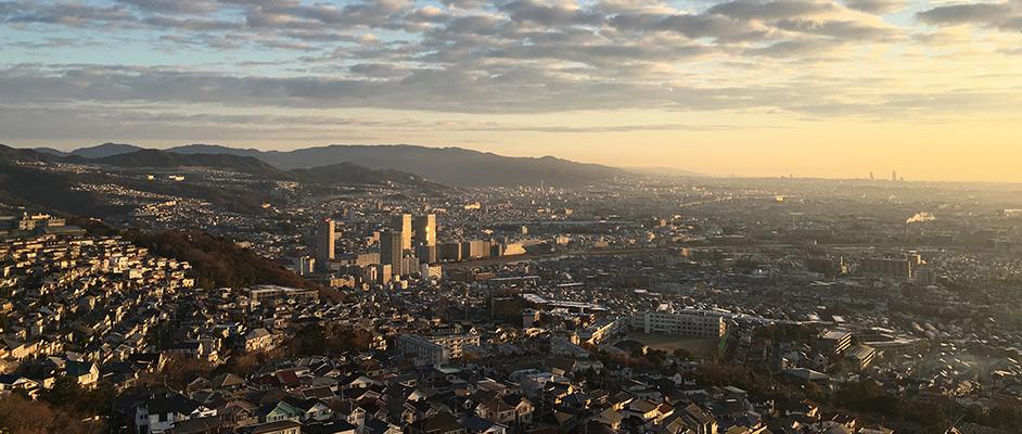 行者山から朝日が差し込む宝塚市内、そして遠景に大阪を望む風景