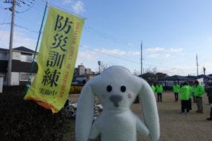 桜公園の入口に防災訓練の旗が立っています。旗の前にまちキョンが到着しました